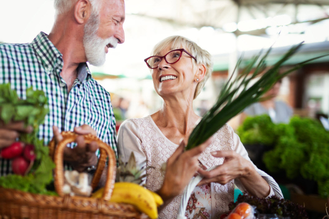 smiling-senior-couple-buying-vegetables-and-at-the-LUGXNK5 web